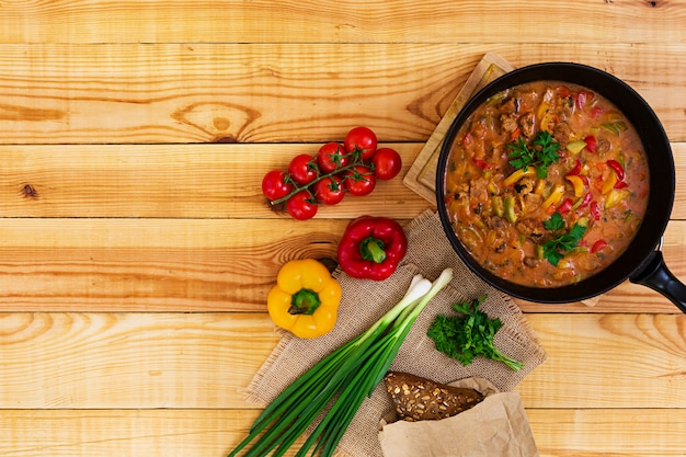 Stew with meat and vegetables in tomato sauce on wooden. top view Premium Photo