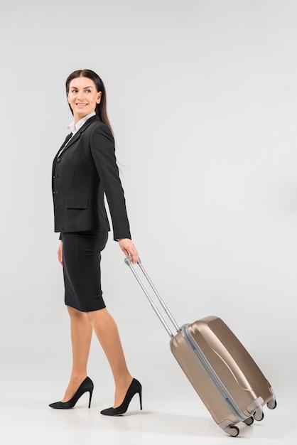 Stewardess with suitcase turning round Free Photo