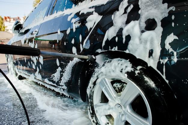 Придерживайтесь разбрызгивания воды на колесо автомобиля Premium Фотографии