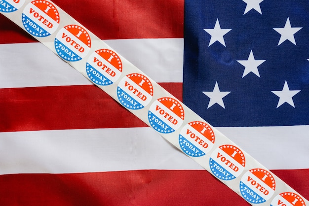 Sticker strip i vote today on the usa flag after voting in the ballot box. Premium Photo