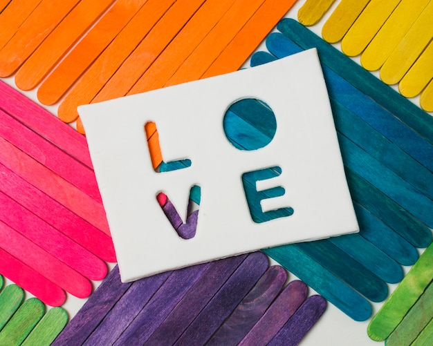 Sticks in bright lgbt colors and love word on tablet Free Photo
