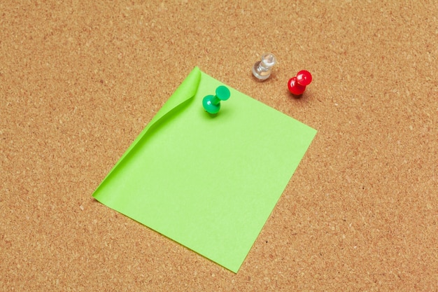 Sticky note pinned on cork board with thumbtacks Premium Photo