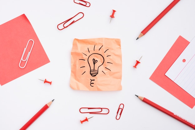 Sticky note with drawn light bulb and office supplies over white background Free Photo