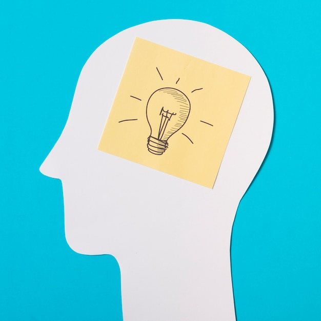 Sticky note with light bulb icon over the paper cut out head Free Photo