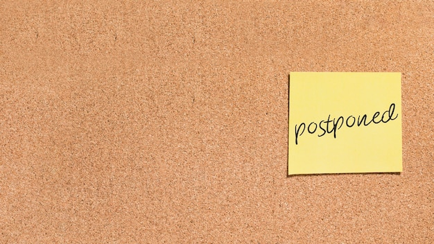 Sticky note with postponed message Free Photo