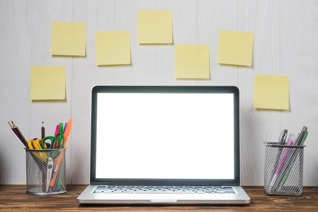 Sticky notes and stationery near laptop Free Photo