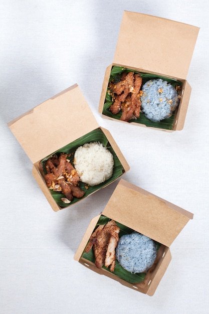 Sticky rice with grilled pork and fried pork put in a brown paper box, put on a white tablecloth, food box, thai food. Premium Photo