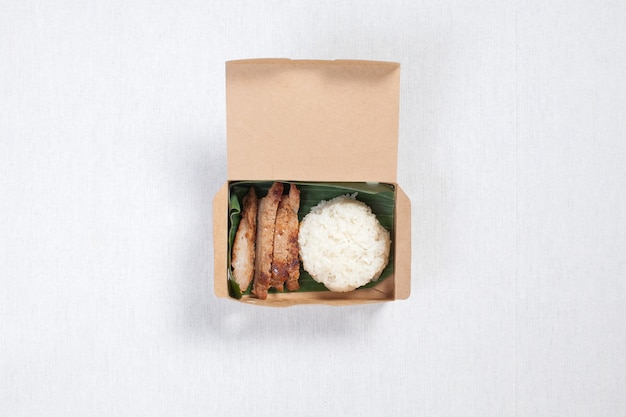 Sticky rice with grilled pork put in a brown paper box, put on a white tablecloth, food box, thai food. Premium Photo