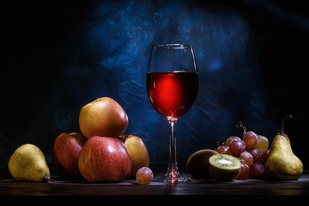 静物、リンゴ、ブドウ、果物、濃紺の背景に赤いジュース。ダイエット、健康的な食事。 Premium写真