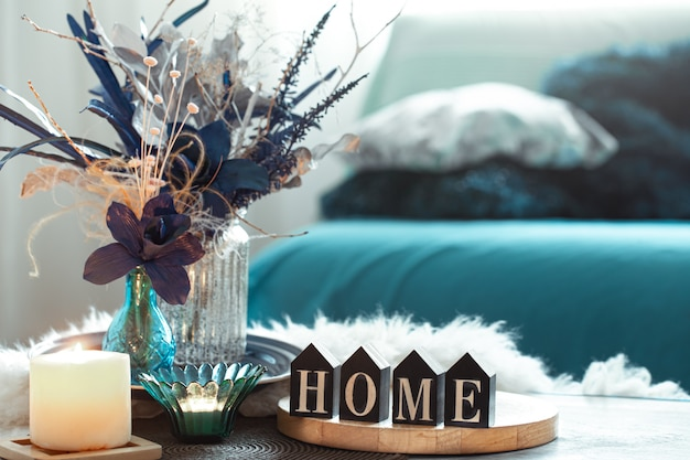 Still life in blue tones, with wooden inscription home and decorative elements in the living room. Free Photo