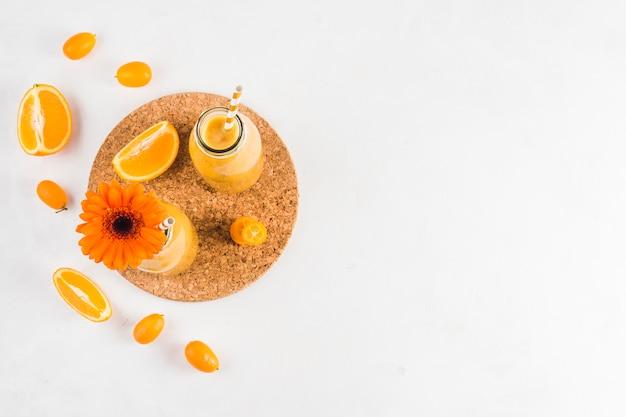 Still life of delicious orange smoothie Free Photo