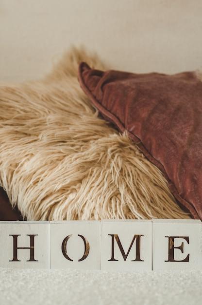 Детали натюрморта в домашнем интерьере гостиной и надпись home. много декоративных уютных подушек. остальное. уютная осенняя или зимняя концепция, трикотаж. домашняя концепция Premium Фотографии