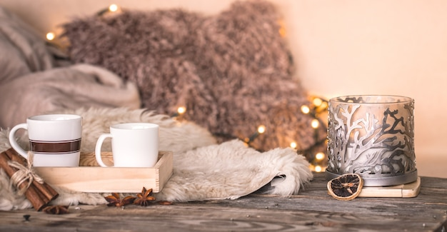 Still life home atmosphere in the interior with cups and candles on the table of cozy bedspreads Free Photo