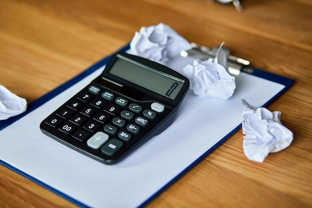 オフィスアクセサリー計算機、紙、ラップトップ、ノートブック、しわくちゃの紙のボールの木製テーブル、会計および銀行サービスを備えた会計士のワークスペースの静物。財政と支払い Premium写真
