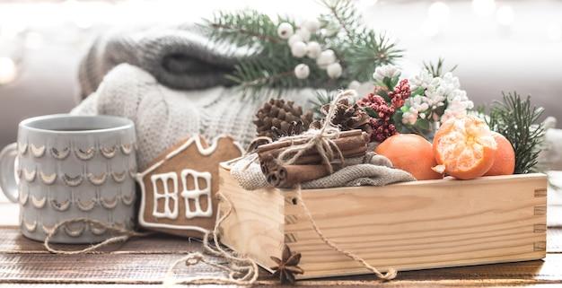 クリスマスの飾りの静物、果物の美しいボウル、クリスマスツリーとニットの服にお祝いのスパイス 無料写真