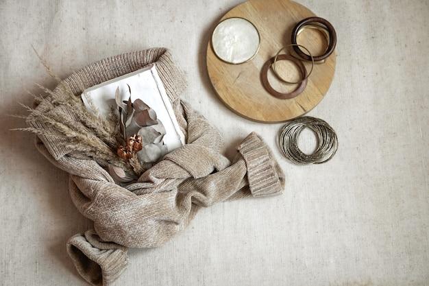 Натюрморт из деталей. букет из засушенных цветов на теплый свитер и женские браслеты, вид сверху, осенняя концепция. Premium Фотографии