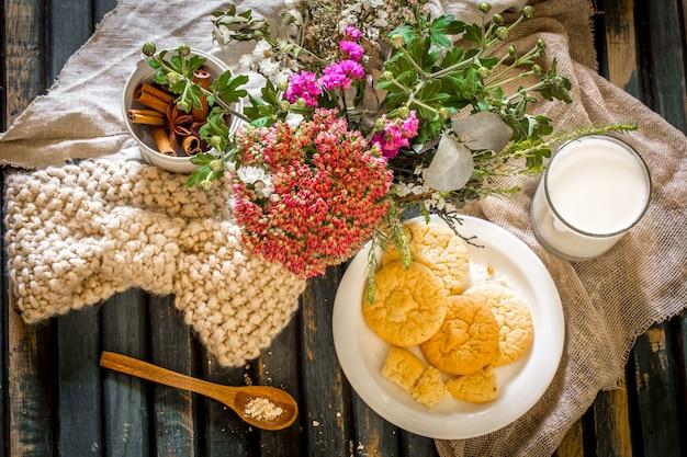 クッキーとガラスの牛乳のプレートと木製のテーブルでの静物 無料写真
