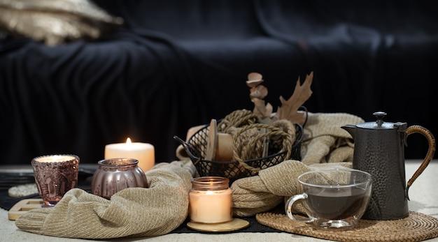 キャンドル、セーターの本、紅葉のあるテーブルの静物。居心地の良いリビングルーム、家のインテリア。 無料写真