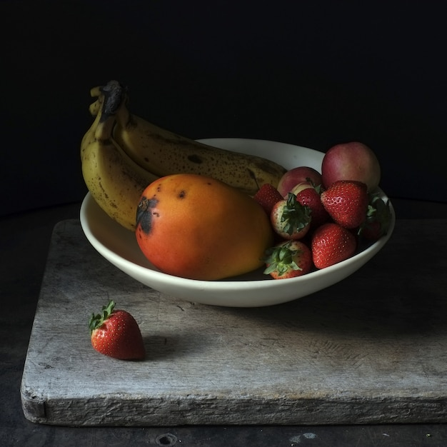 Still life photography of fresh fruits in a white plate on black background Free Photo
