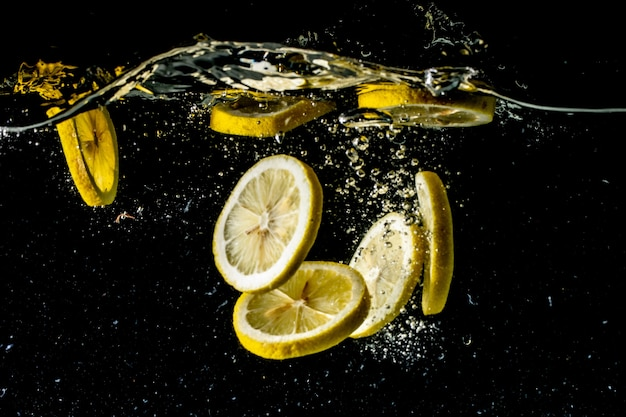 Still life photography shot of lemon slices falling under the water and making a big splash Free Photo