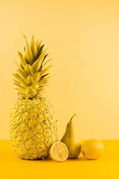 Still life of pineapple; lemon and pears against yellow backdrop Free Photo