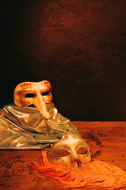 Still life of venetian carnival mask with feathers against dark textured background Free Photo