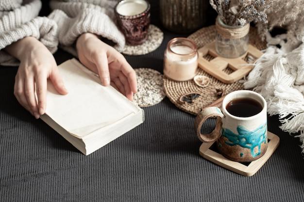 Натюрморт с красивой чашкой и женскими руками. интимная домашняя атмосфера. декоративные элементы. Бесплатные Фотографии