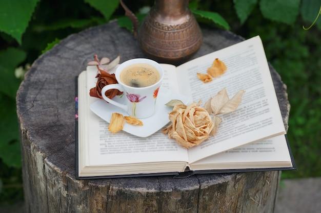 緑の植物で覆われたアンティークピッチャー、開いた本、一杯のコーヒーのある静物 Premium写真