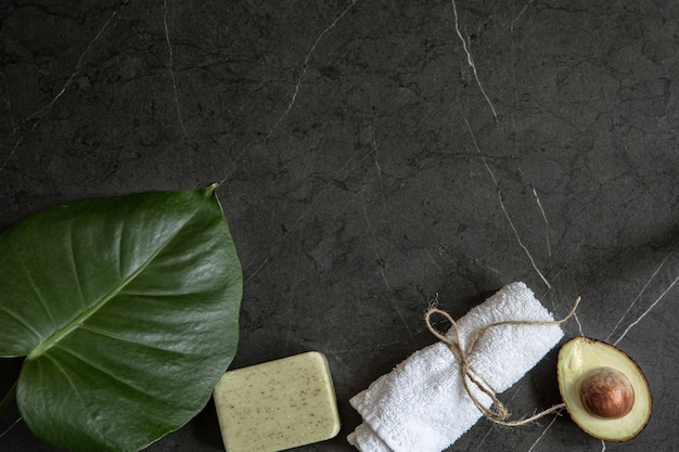 Still life with avocado, towel and soap on a dark marble surface copy space. face and body skin care concept. Free Photo