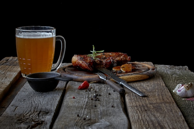 Still life with a big fried steak, a glass of beer, mustard and cutlery on an old wooden tabletop, the concept of oktoberfest Premium Photo