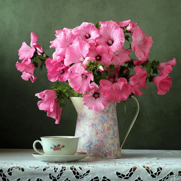 Still-life with a bouquet in the retro jug and cup on the table Premium Photo
