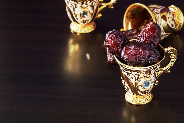 Still life with dates and golden traditional arabic coffee set with mini cup. Premium Photo