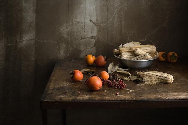 木製の古いテーブルの上のアルミボウルに果物とトウモロコシの静物 Premium写真