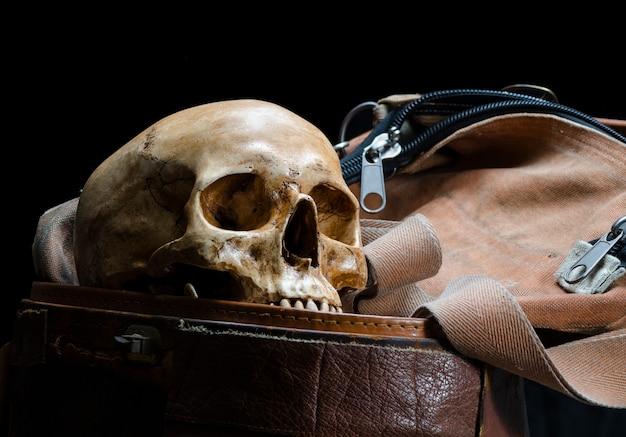 人間の頭蓋骨のある静物は黒の背景に分離された古い革箱に配置されます。 Premium写真