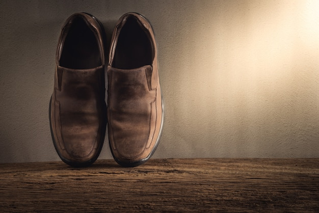 Still life with men's shoes on wooden tabletop against grunge wall Premium Photo