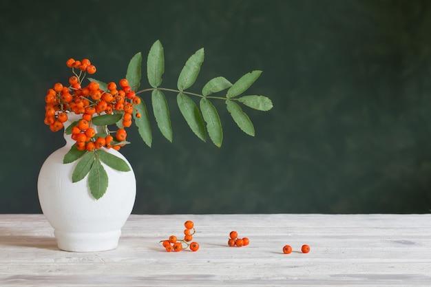 Натюрморт с ягодами рябины на темном фоне Premium Фотографии