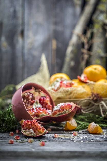 Still life with tangerines and pomegranate on wood Free Photo