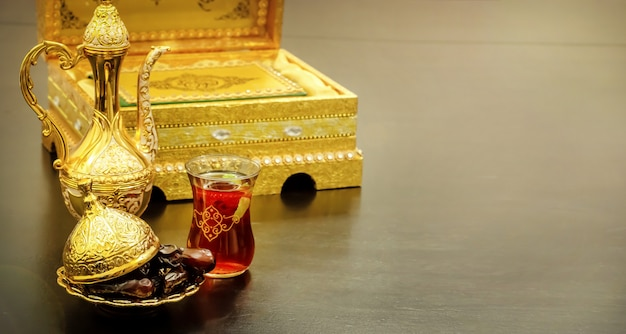 Still life with traditional luxury golden arabic coffee set with dallah, cup and dates. quran book. ramadan concept. Premium Photo