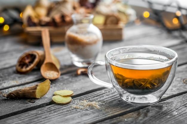 木製の背景上のお茶の透明なカップのある静物 無料写真