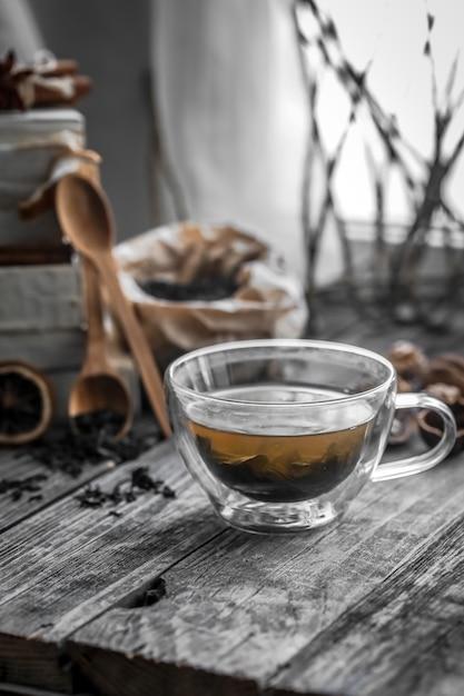 Натюрморт с прозрачной чашкой чая на деревянном фоне Бесплатные Фотографии