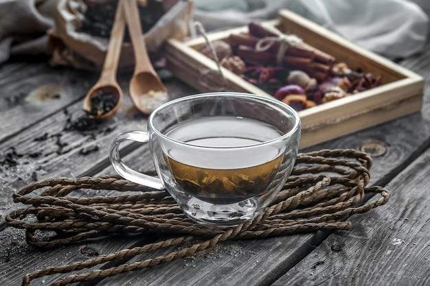 Still life with transparent and fragrant cup of tea with ginger on wooden background Free Photo