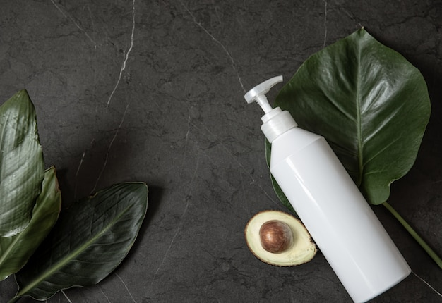 Still life with white cosmetic dispenser bottle mockup with avocado and leaves top view. beauty and hygiene concept. Free Photo