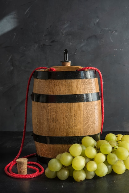 Still life with white wine, bottle and barrel Premium Photo