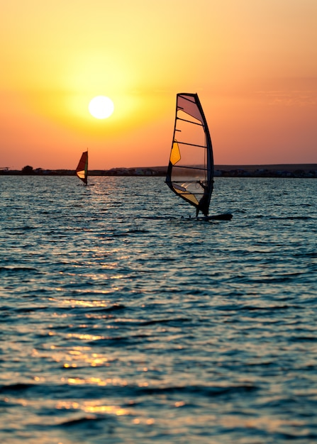 Still sea surface, man practicing wind surfing and golden sunset in sky Premium Photo
