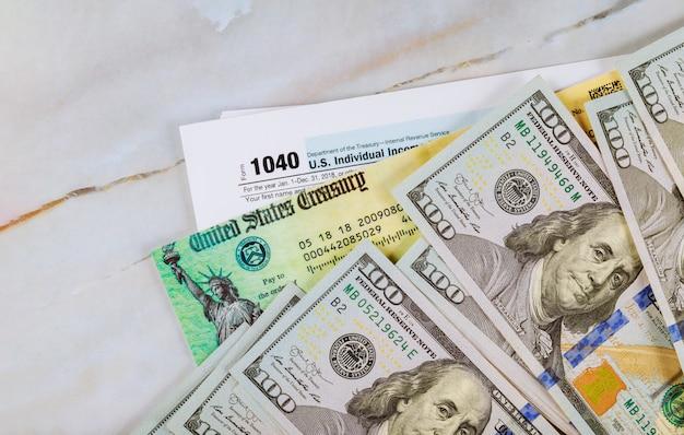 Stimulus economic tax return check and us 100 dollar bills currency Premium Photo