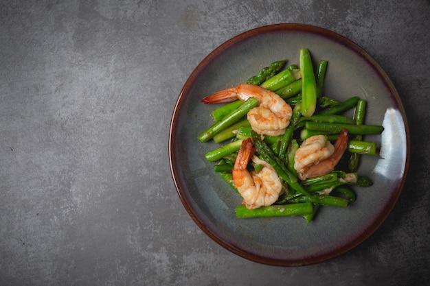 Stir fried asparagus and shrimp on table. Free Photo