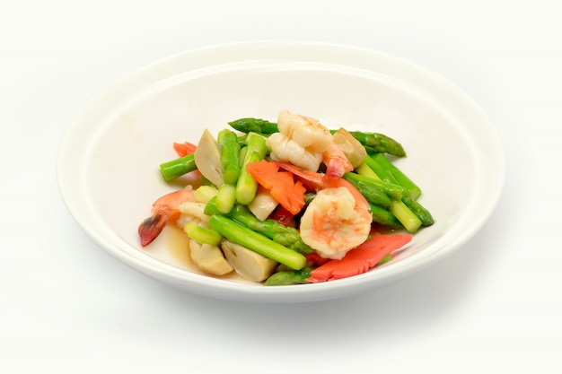 Stir fried asparagus with shrimp on white plate and white background. Premium Photo