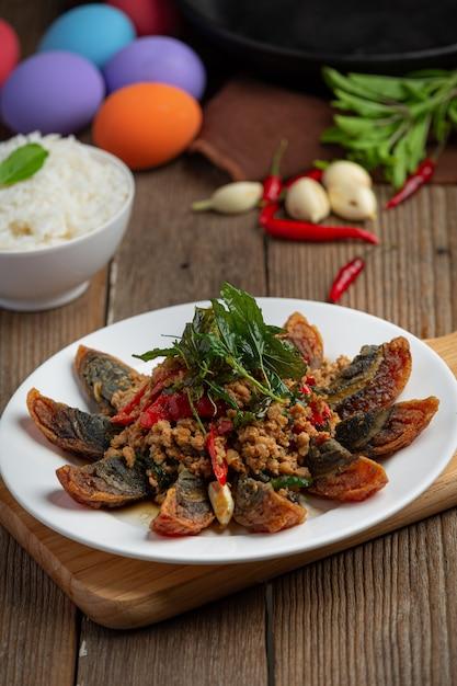 Basilico saltato in padella con uovo piccante del secolo servito con riso al vapore e salsa di pesce al peperoncino, cibo tailandese. Foto Gratuite