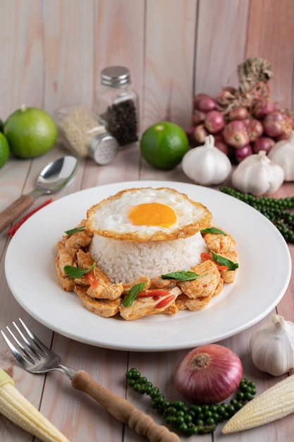 나무 테이블에 흰 접시에 쌀 튀긴 계란과 튀긴 칠리 붙여 넣기 치킨을 저 어. 무료 사진