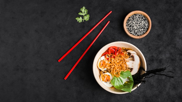 Stir-fried chinese noodles with vegetables and eggs on black textured backdrop Free Photo